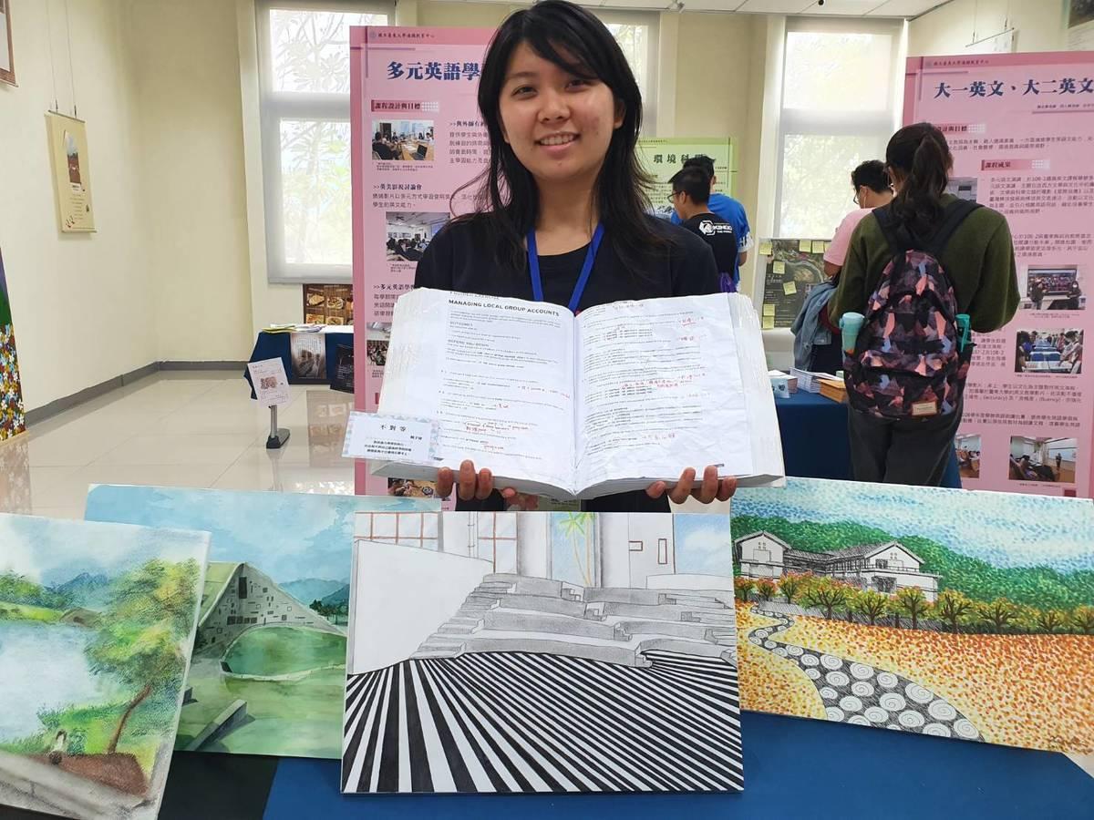 資工系學生開心展示她在通識教育藝術概論課程中創作的作品。